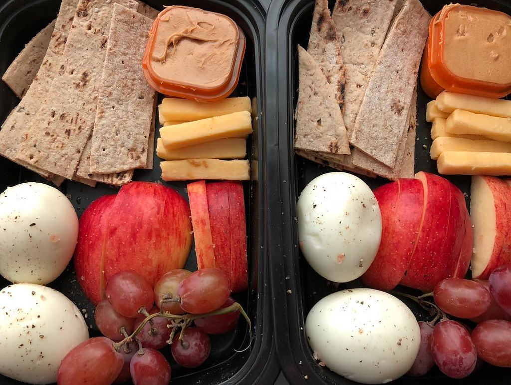 Bread, apples, grapes, cheese, peanut butter, and two hard boiled eggs are seen in Starbucks' Protein box.
