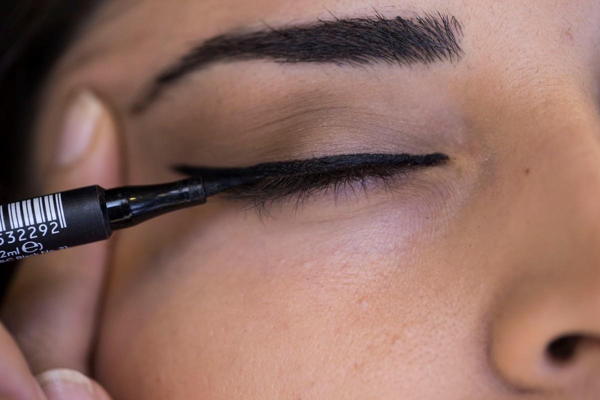 A woman applies eyeliner.