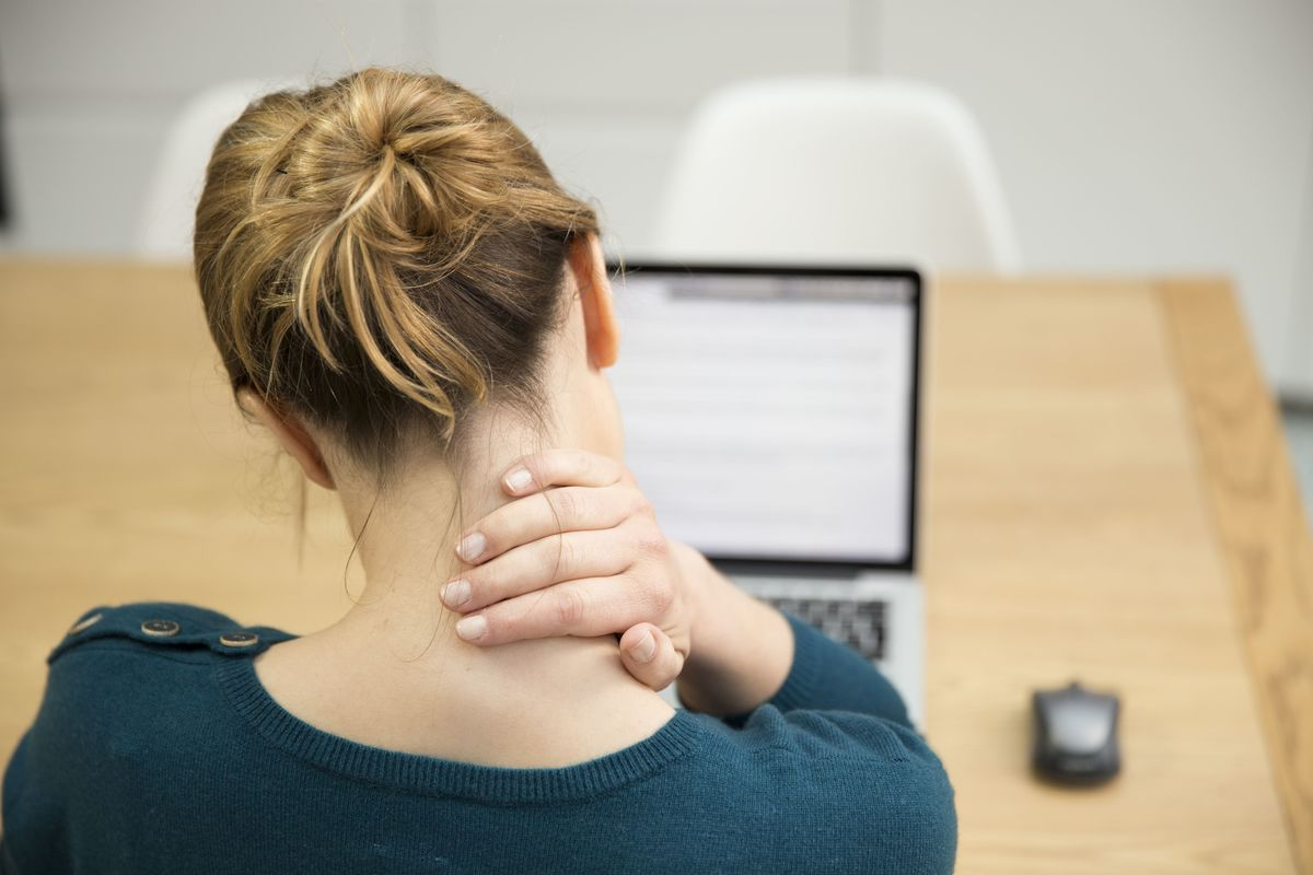 A woman rubs her neck while looking at a computer.