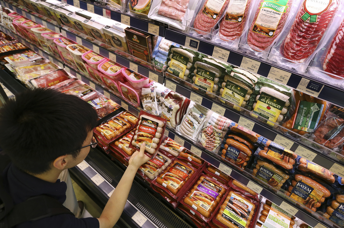 A customer chooses pre-cooked sausages at a grocery store.