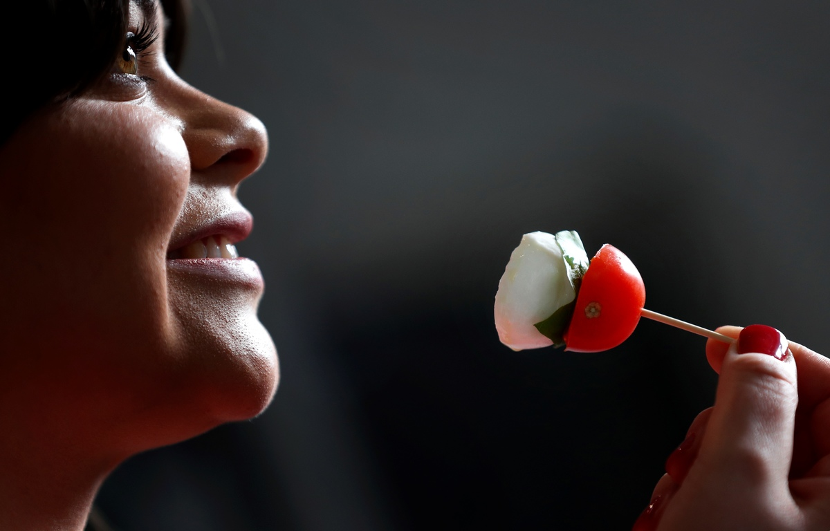 A woman prepares to eat mozzarella cheese with tomato on a toothpick.