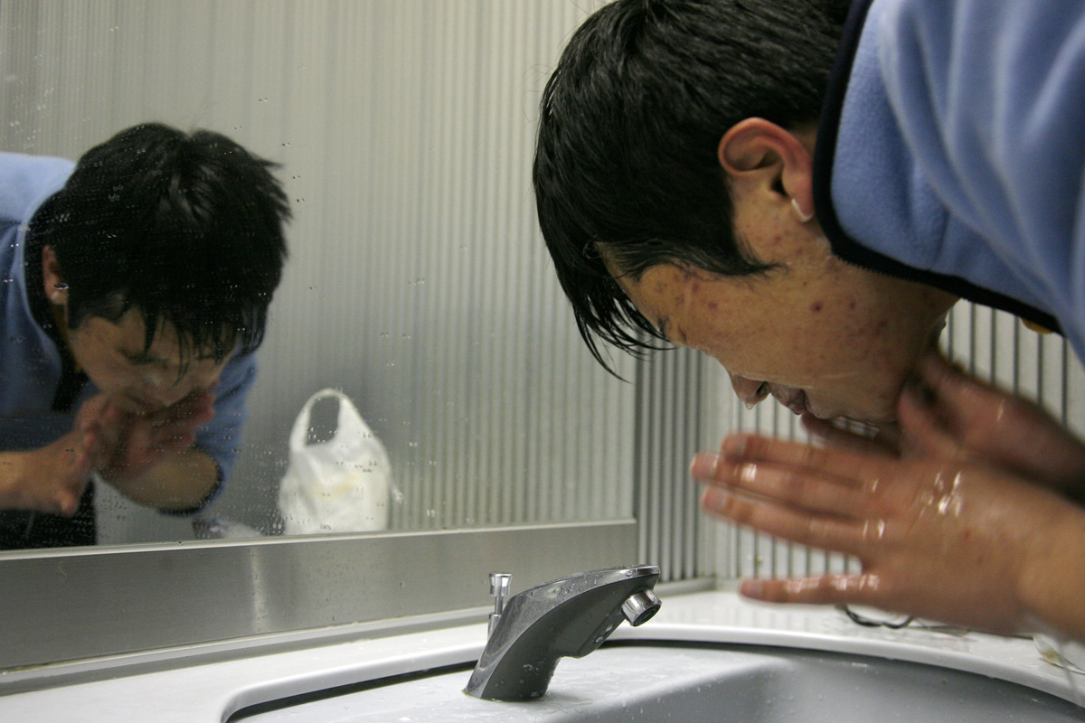 A man washes his face in a sink.