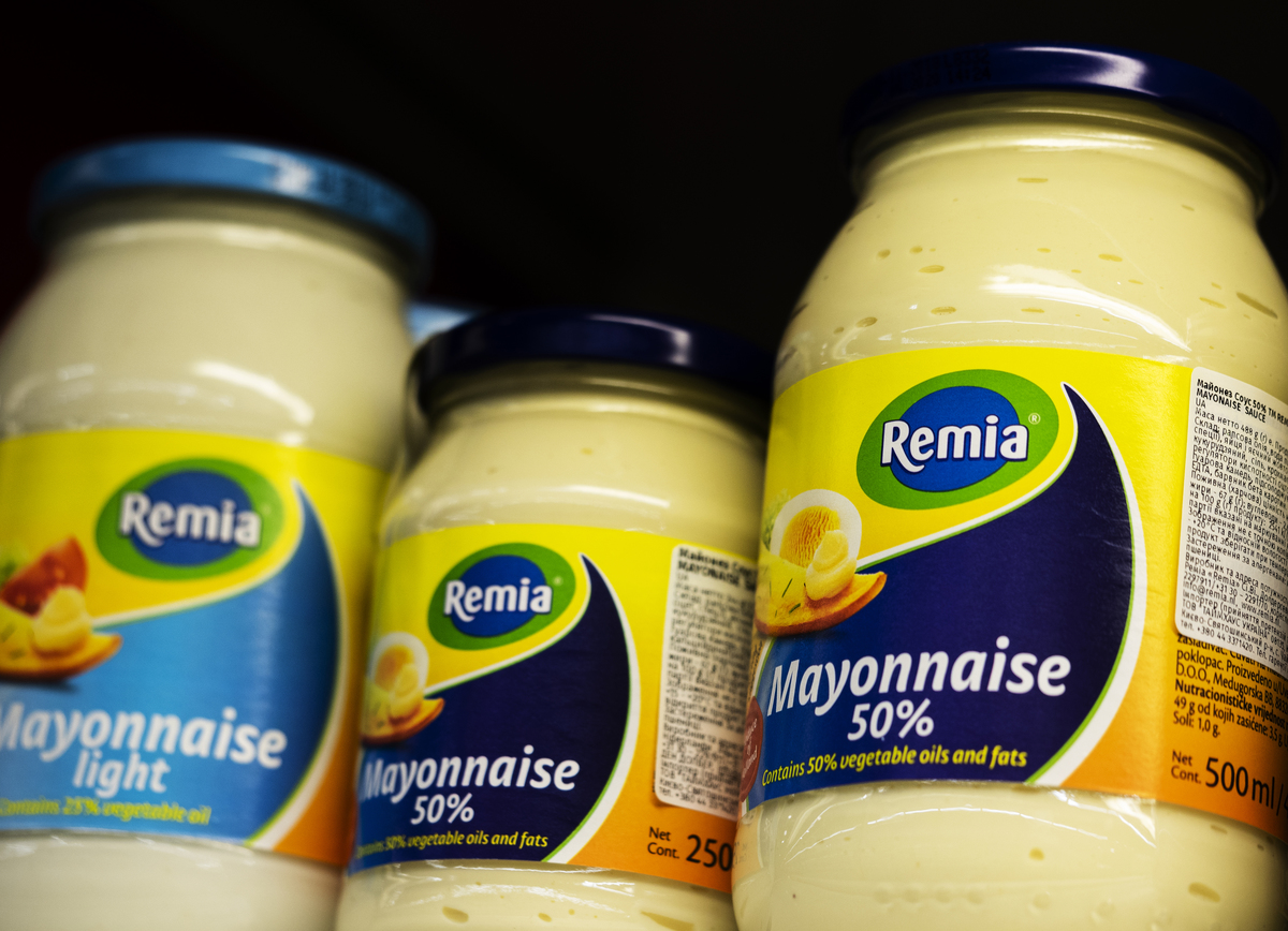 Jars of mayonnaise sit on a grocery store shelf.