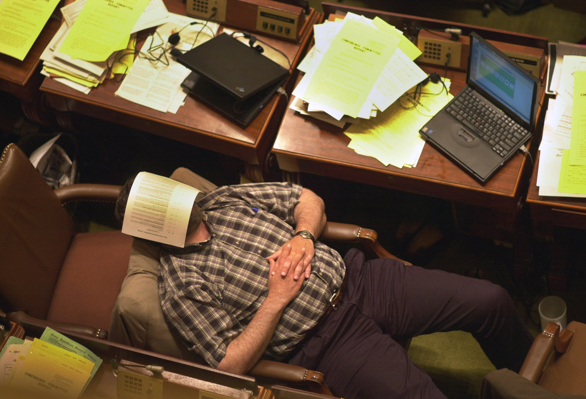 A man with a piece of paper over his face lies asleep at his desk chair.
