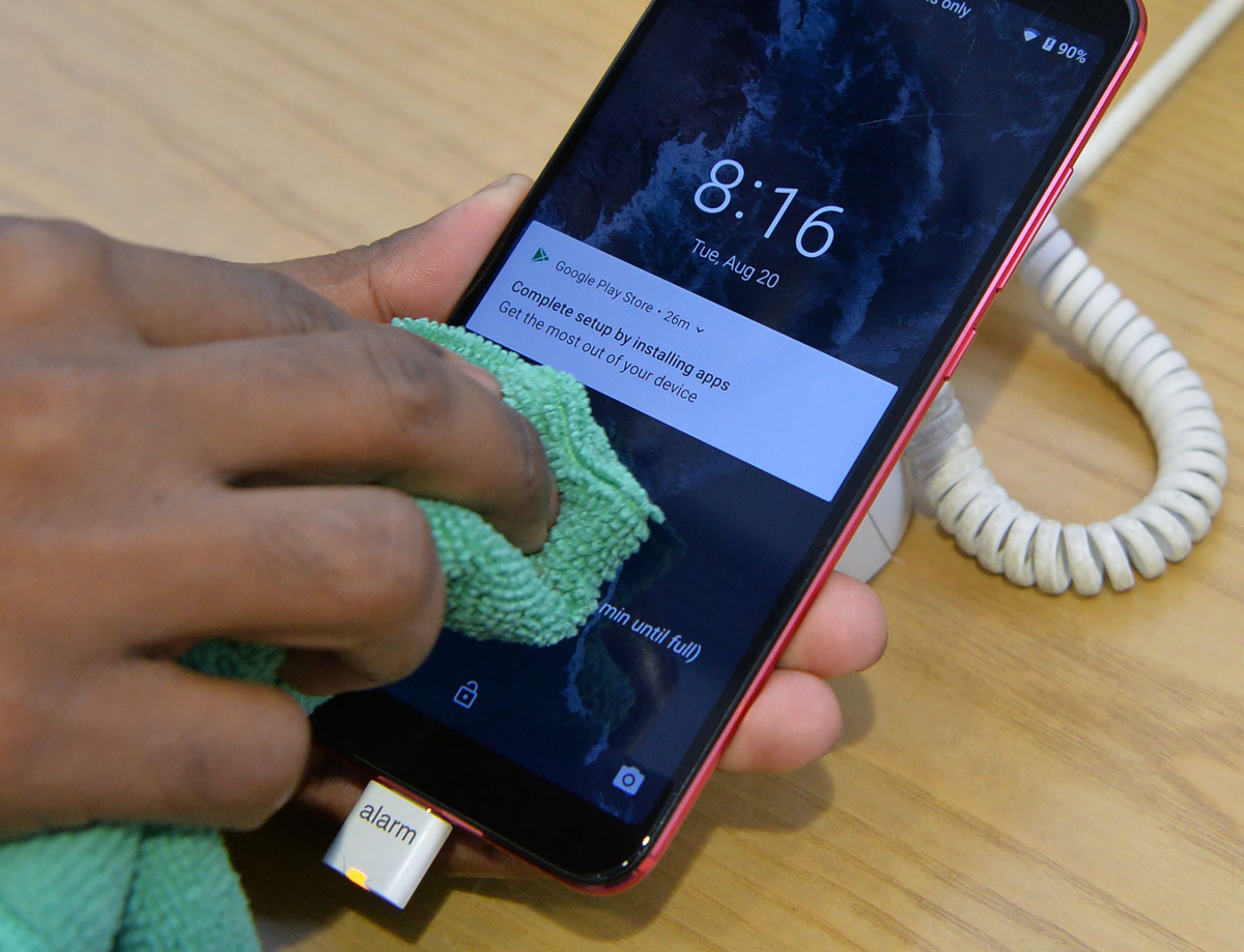 A person cleans their phone with a cloth.