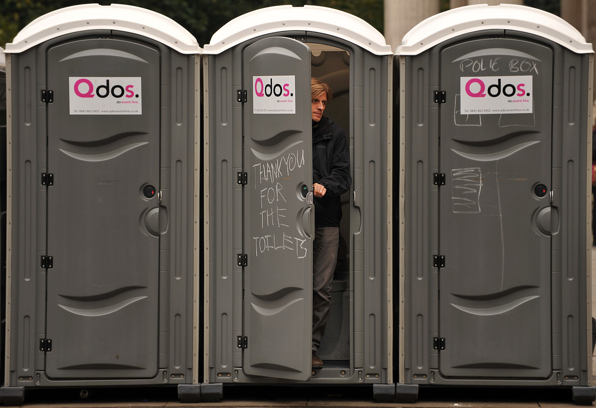 A man leaves a portable toilet.