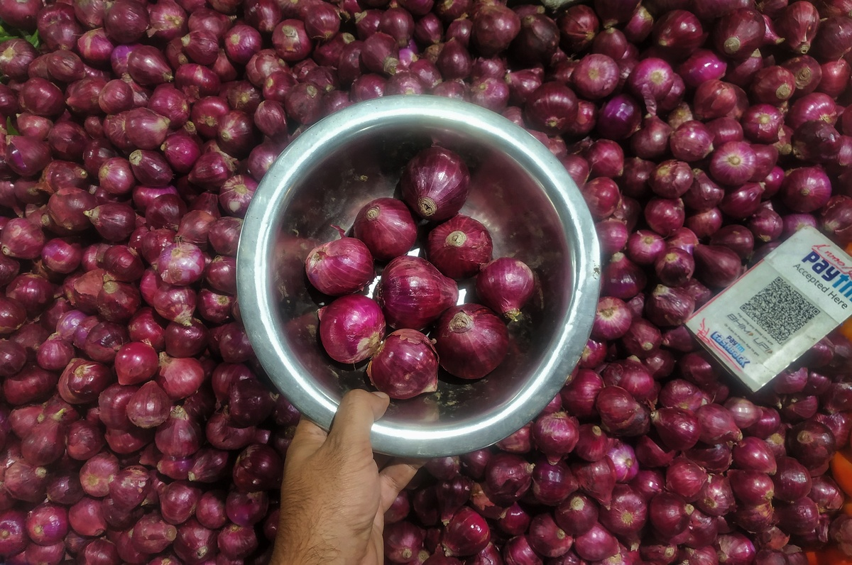A customer grabs a bowl of red onions from a market.