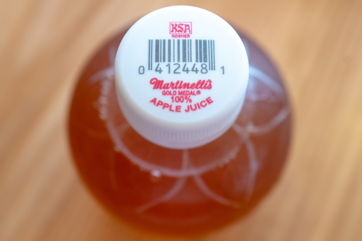 A close-up of a bottle of apple juice is seen.