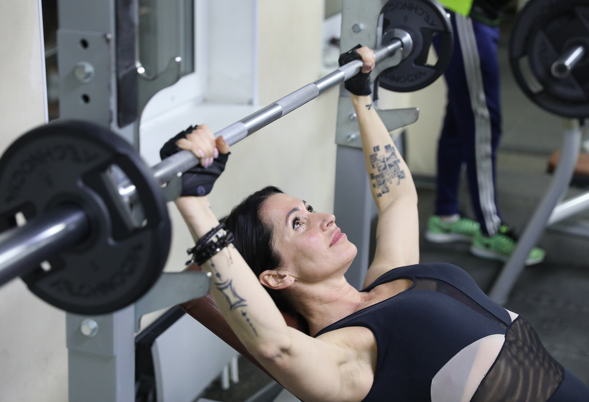 A woman with makeup on lifts weights.