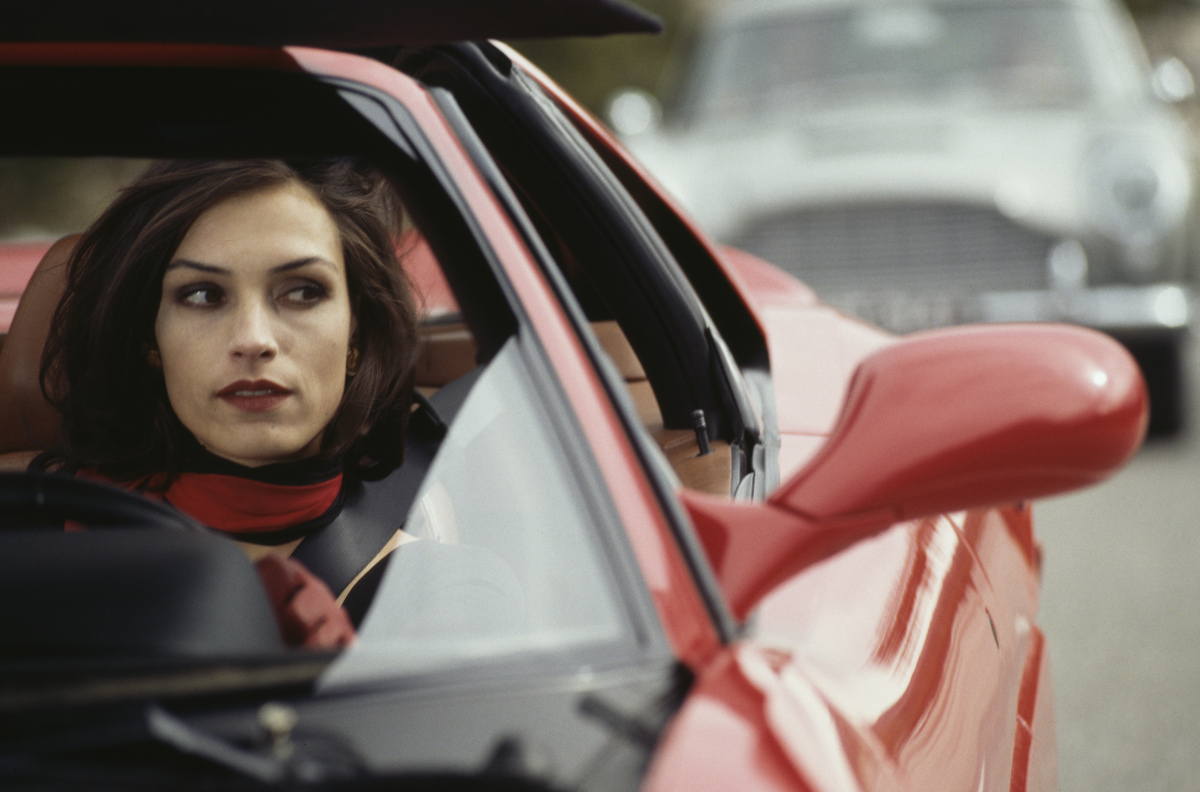 A woman looks out the window as she drives a red Ferrari.