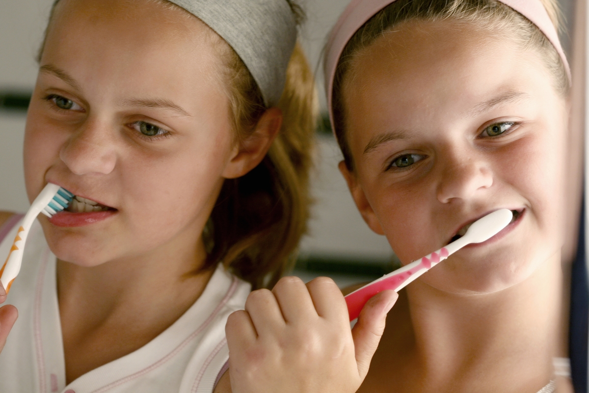 Two girls brush their teeth together.