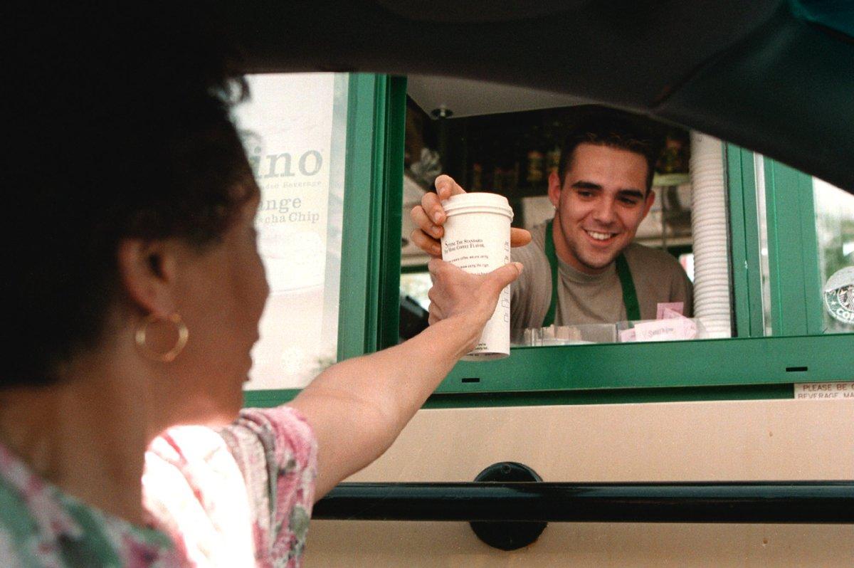 A Starbucks coffee employee hands a customer coffee through a drive-thru.