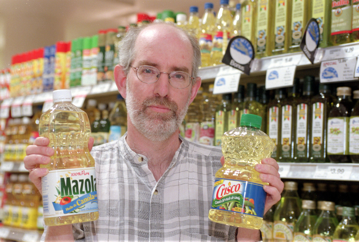 A man holds up canola oils in a grocery store.