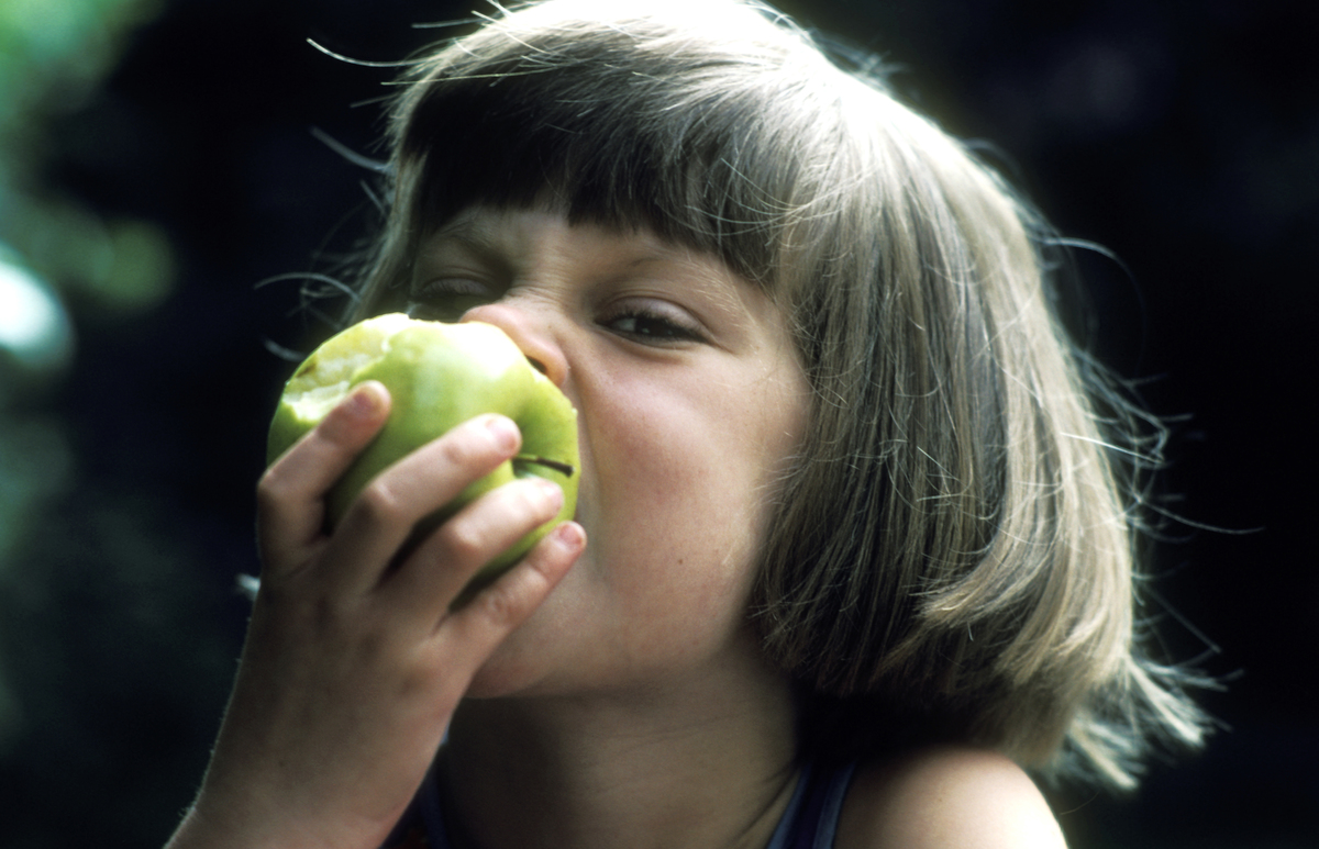 A small girl eats a green apple.