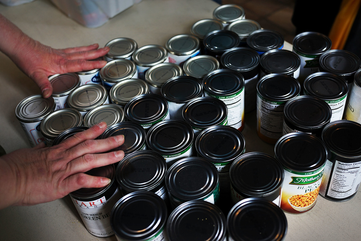 A volunteer organizes cans of food at a soup kitchen.