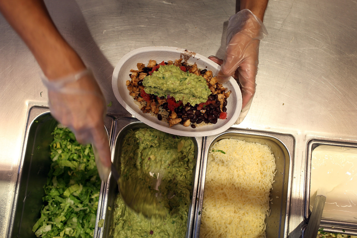 A Chipotle worker fills a chicken and black bean bowl with guacamole.