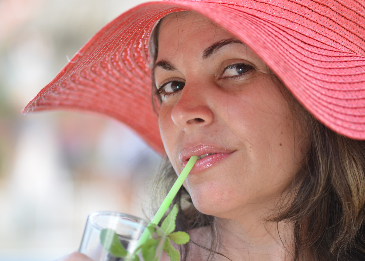 A woman in a hat sips a drink through a straw.