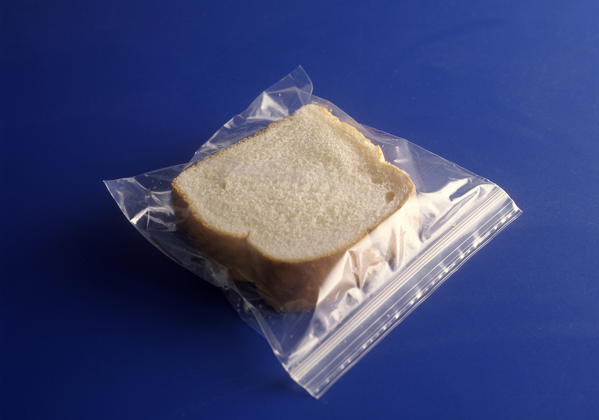 Two slices of white bread are in a ziplock bag against a blue background.