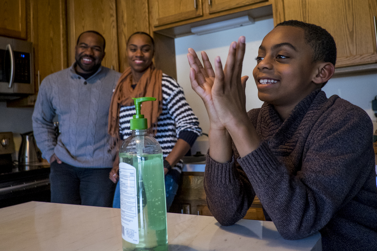 A boy uses hand sanitizer at a kitchen table as his parents smile in the background.
