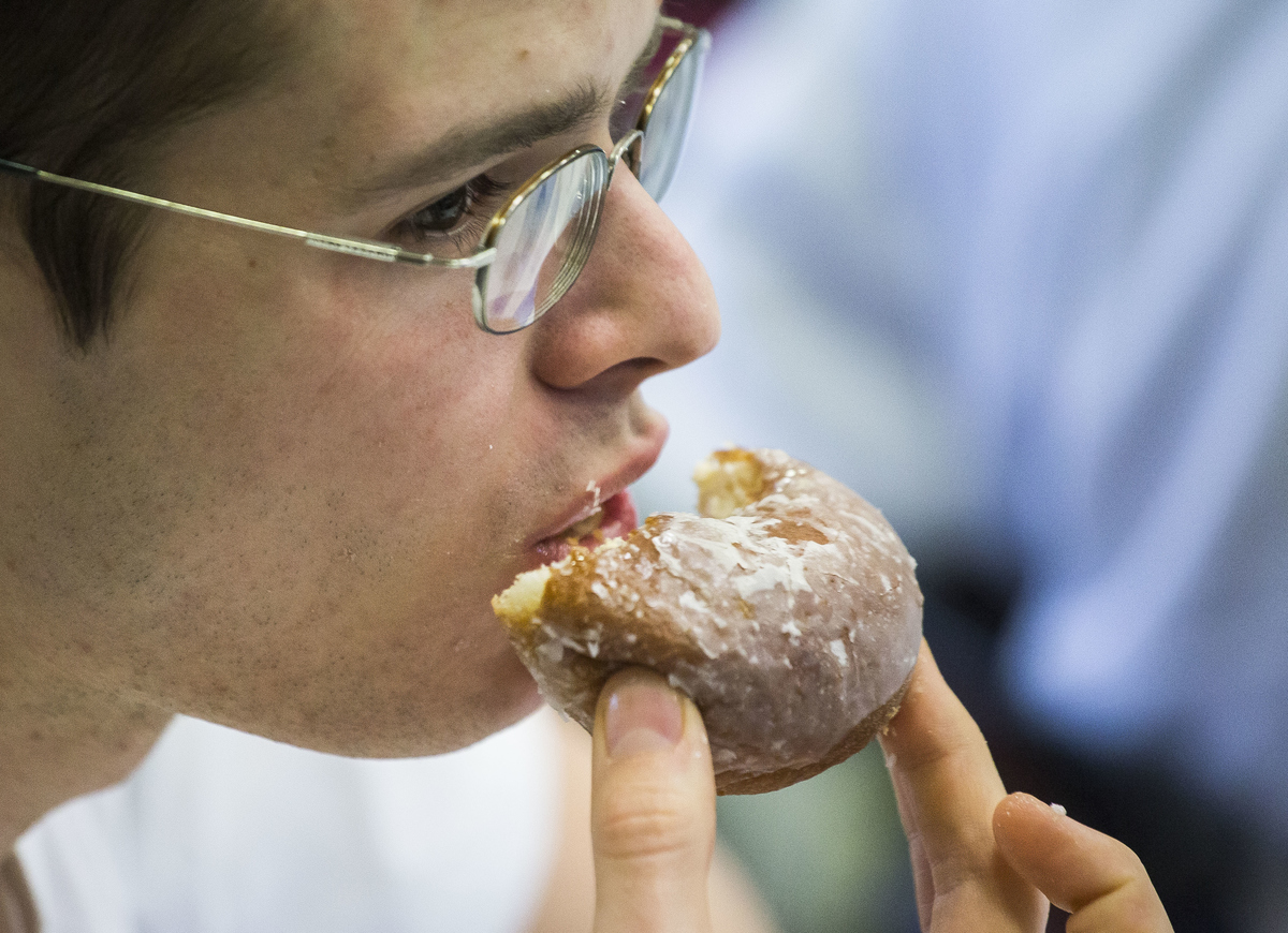 Close-up shows a man eating a donut.