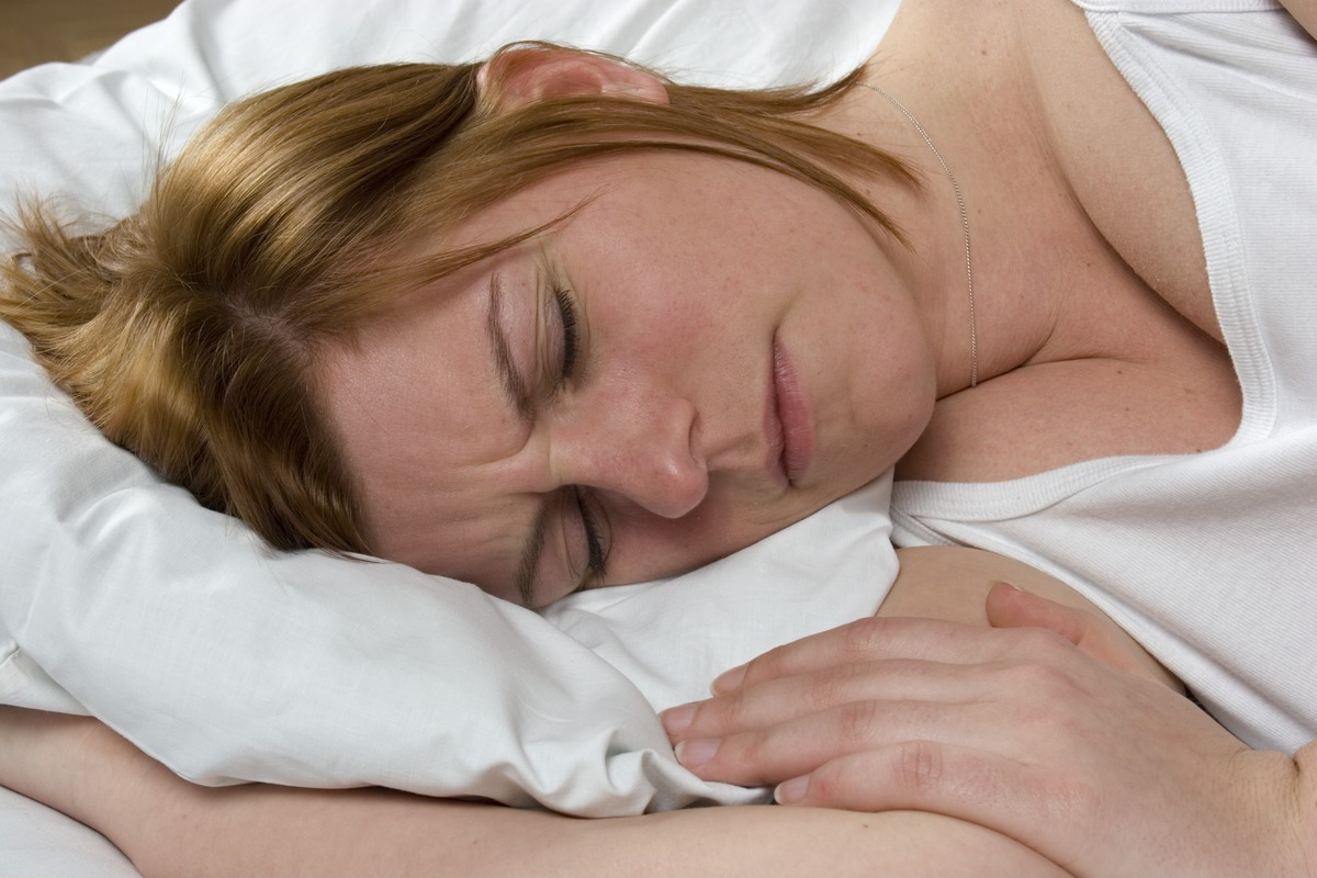 A woman scrunches her face as she struggles to sleep.