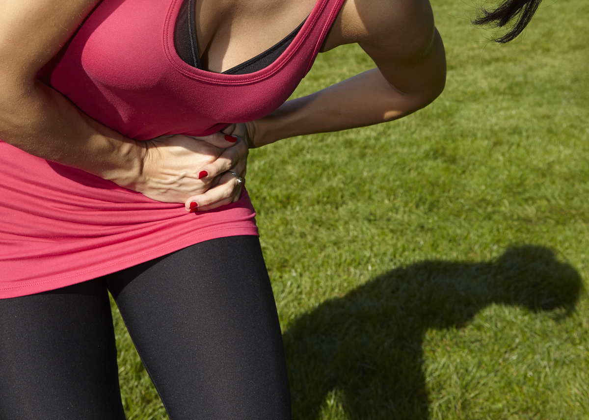 A jogger clutches her side in pain.