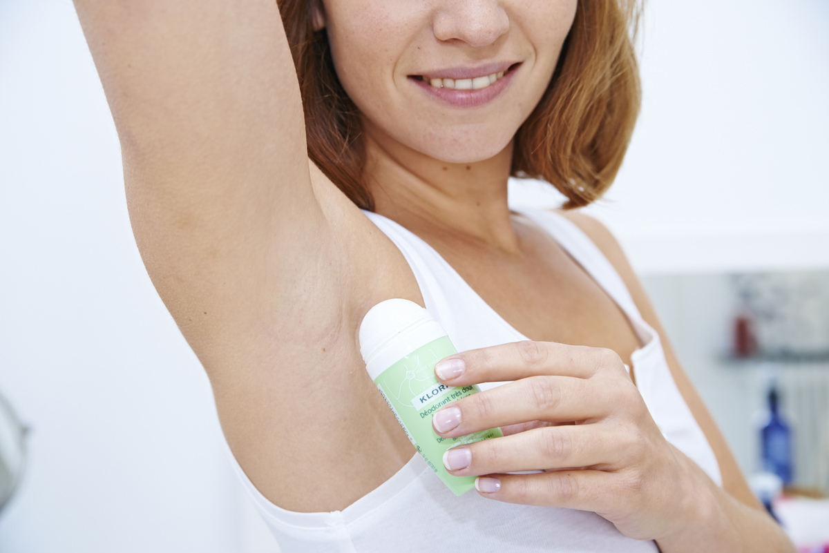 A woman applies roll-on deodorant.