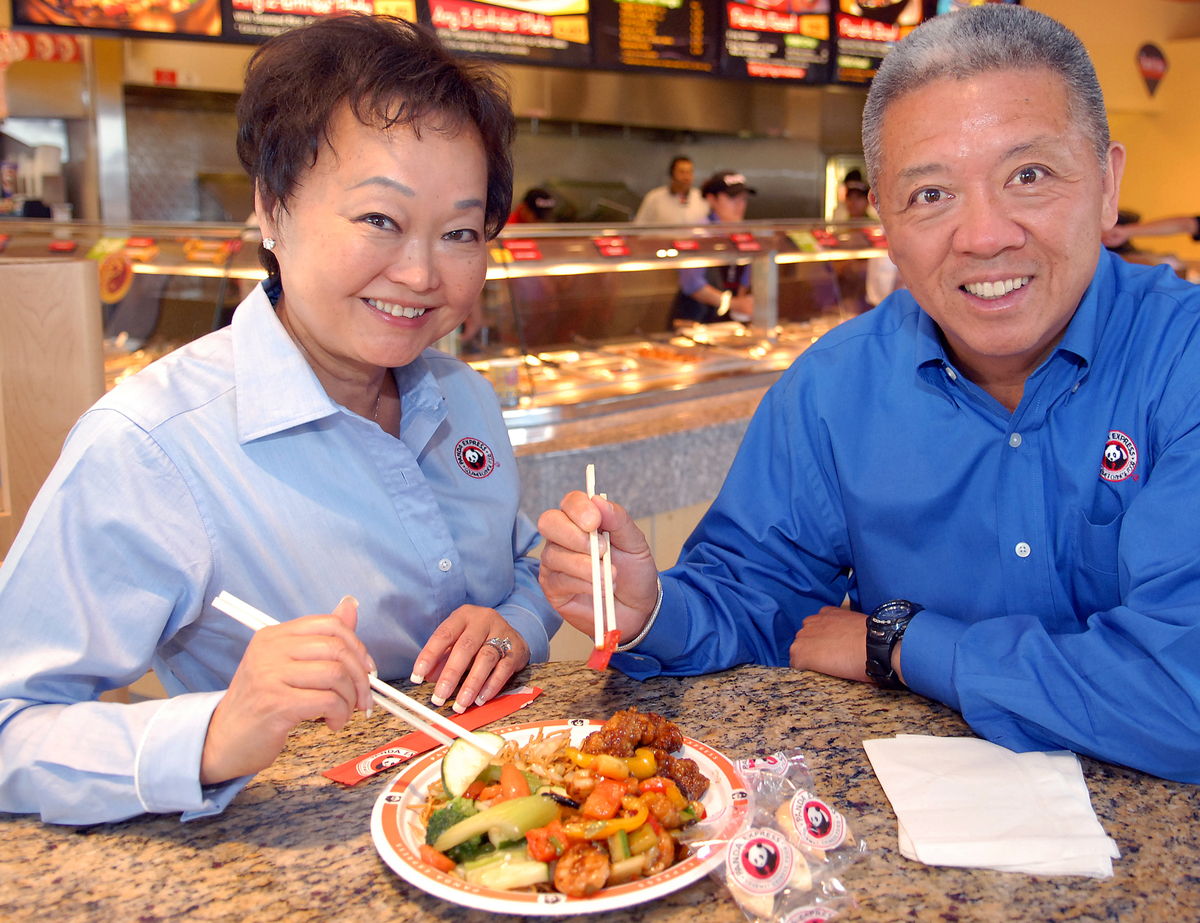 Two restauranteurs smile as they share a plate from Panda Express.