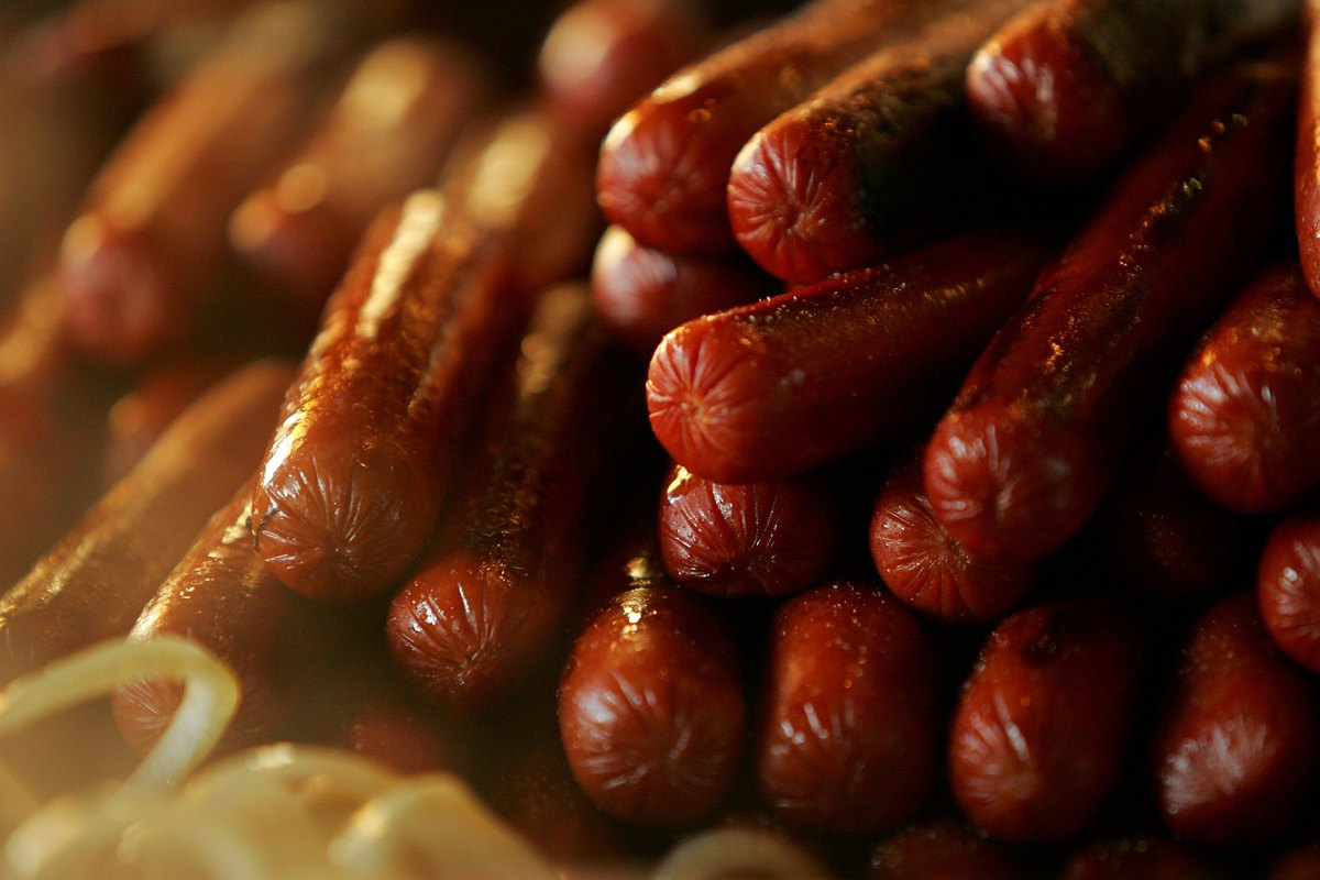 A close-up shows grilled hot dogs in a pile.