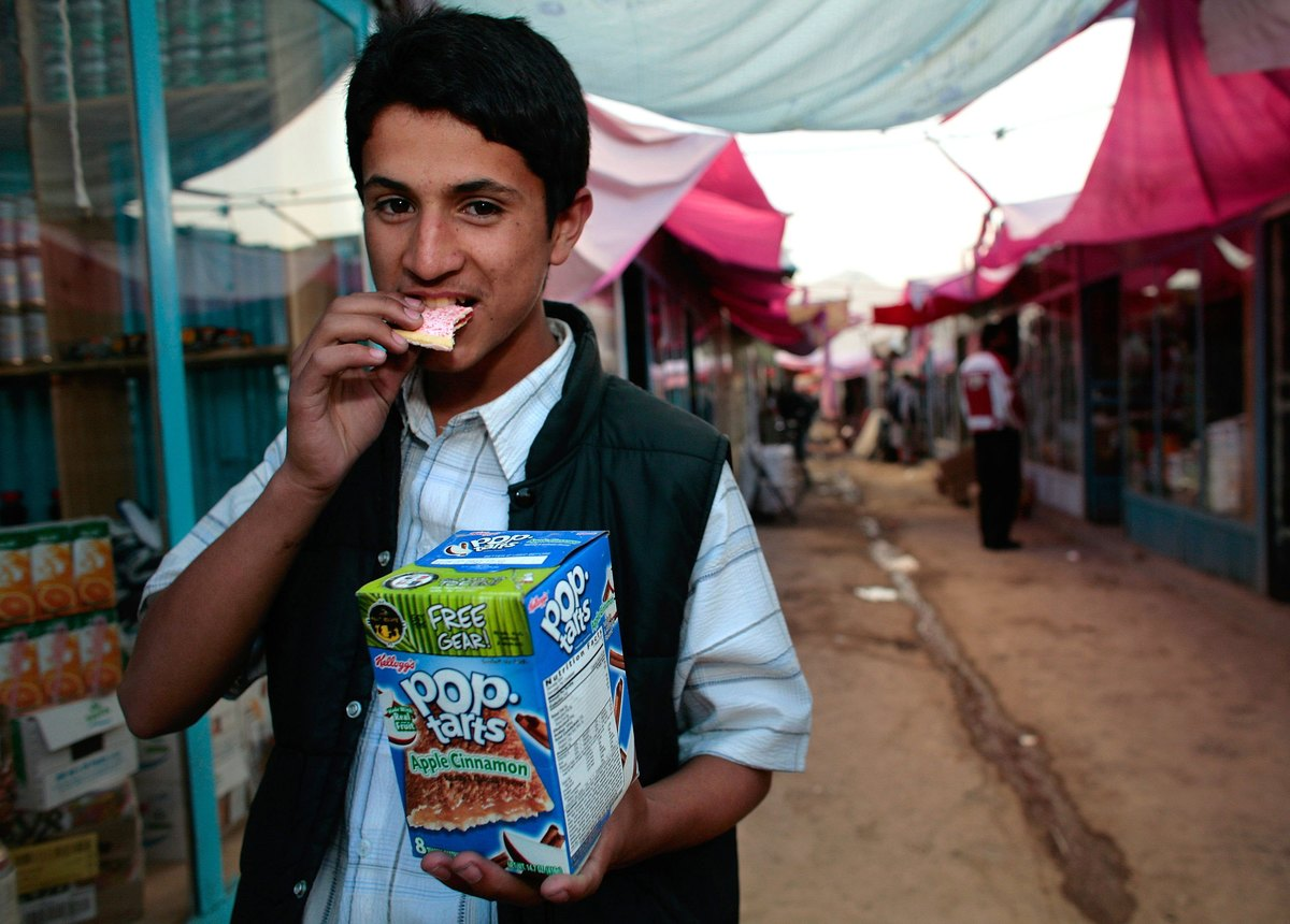 An Afghan merchant eats a Pop-Tart outside of his shop.