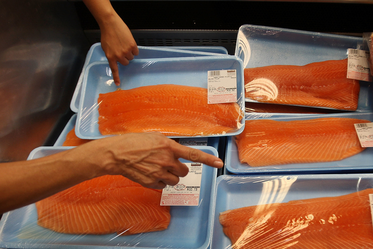 Shoppers choose between salmon fillets at a grocery store.