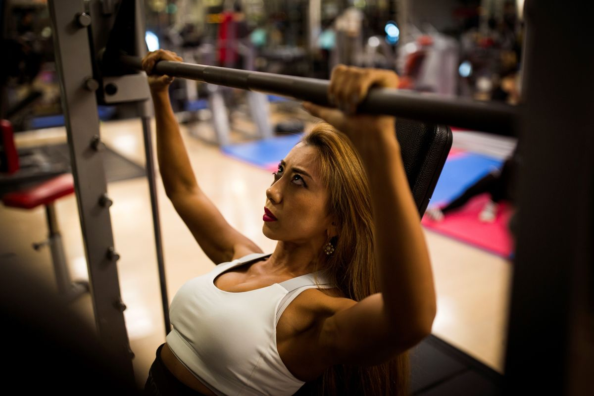 A woman lifts weights in the gym.