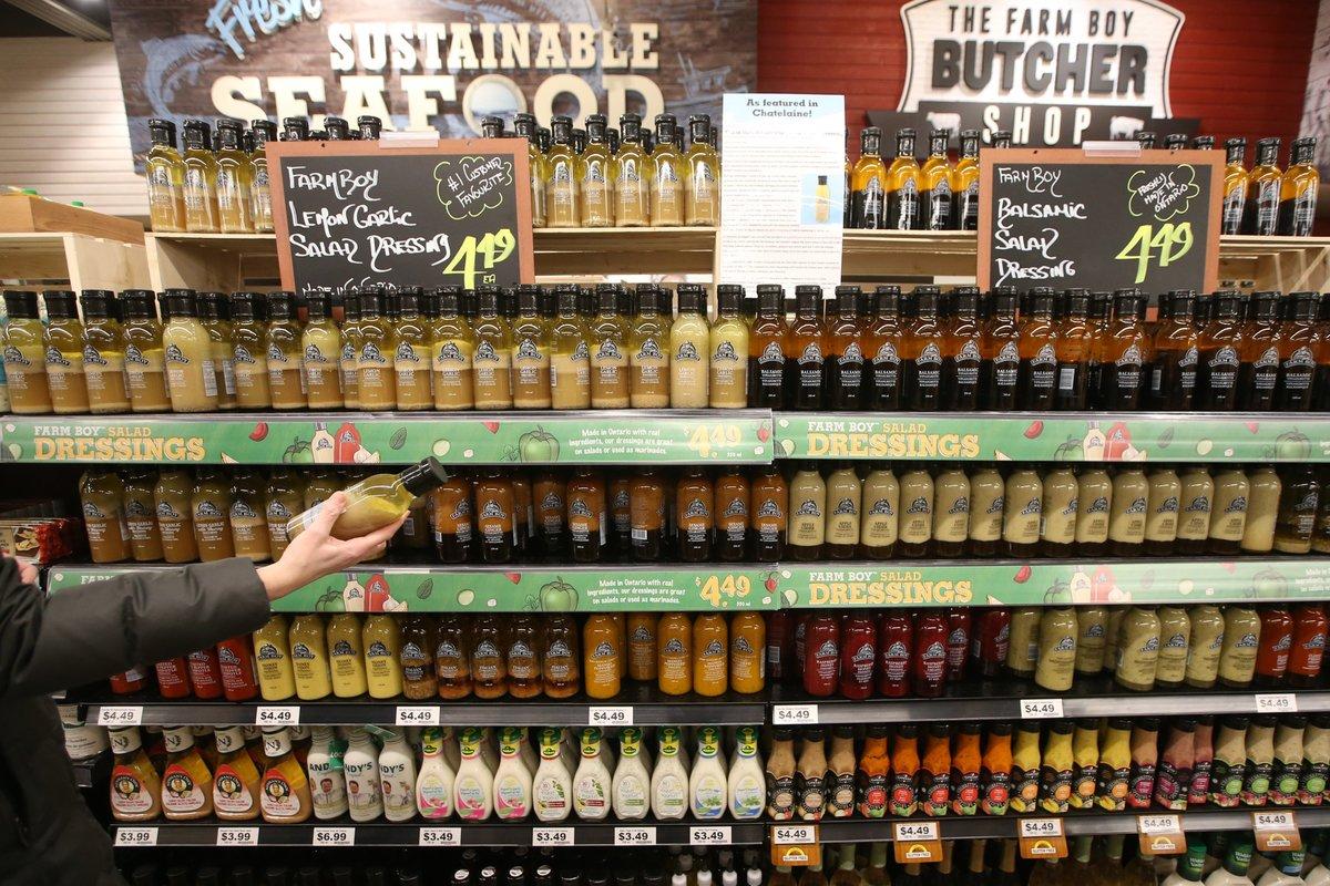 A customer browses shelves of salad dressings in a supermarket.