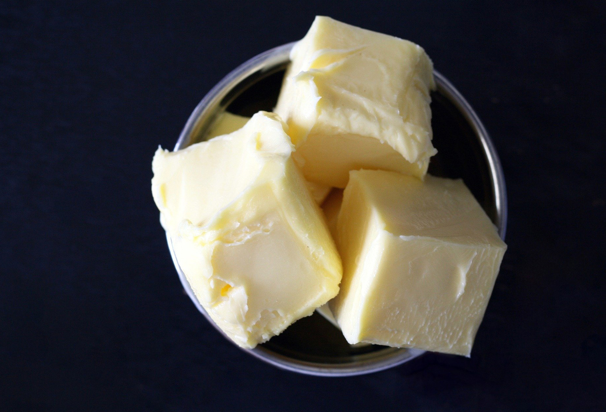 Three cubes of butter sit in a glass bowl.
