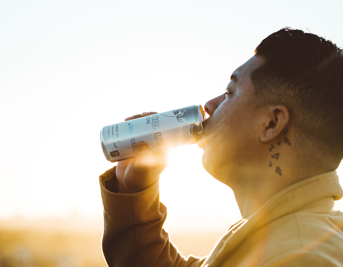 A man enjoys an energy drink as the sun glares in the background.