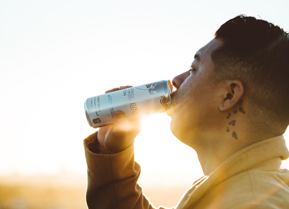 A man sips an energy drink.