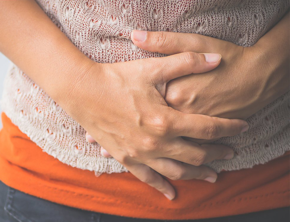 A woman clutches her stomach from bloating.
