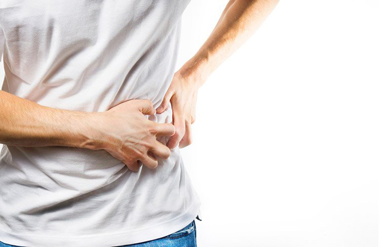 A man clutches his side due to gallstone pain.