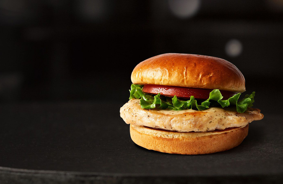 McDonald's artisan grilled chicken sandwich is seen against a black background.