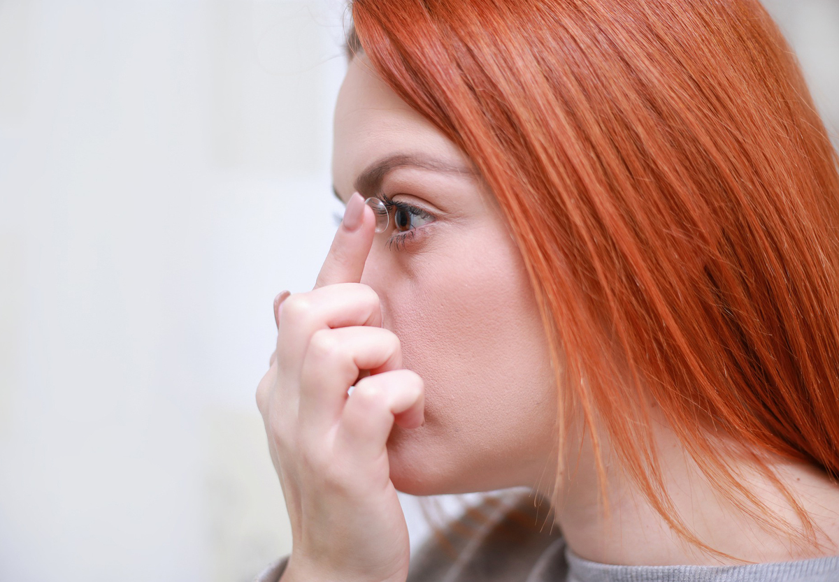 A woman puts in a contact lens.