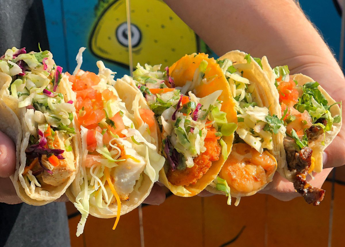 A person holds a long line of Wahoo's fish tacos.