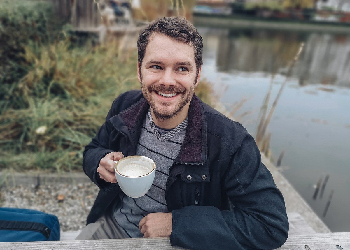 A man drinks a latte while sitting by the lake.