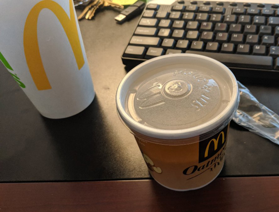 A container of McDonald's oatmeal sits on a desk next to a drink.