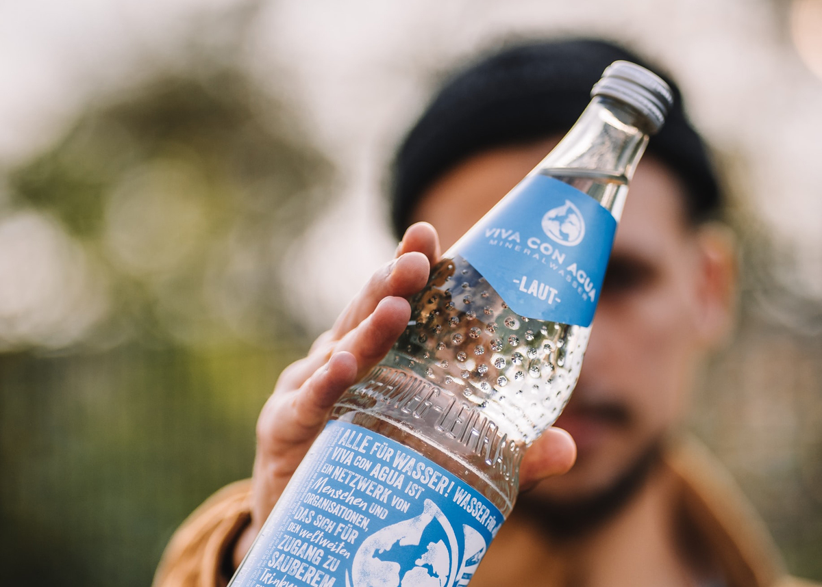 A man holds out a bottle of mineral water.