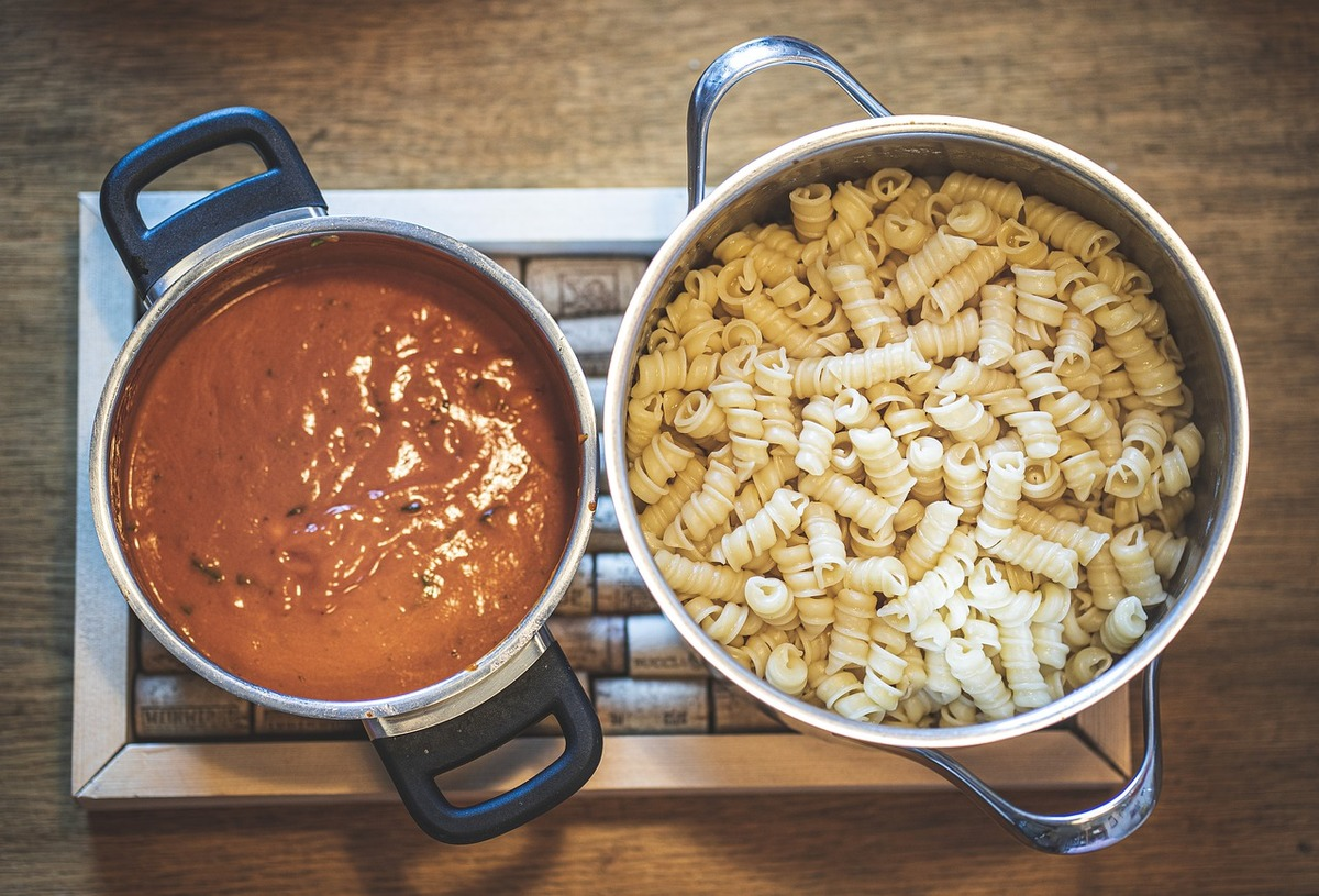 The pot on the left contains pasta sauce, while the pot on the right contains noodles.