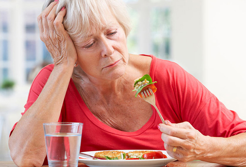 An older woman shows no interest in eating.
