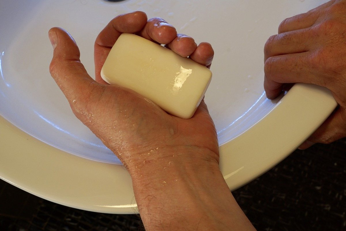 A person holds a bar of soap over a tub.