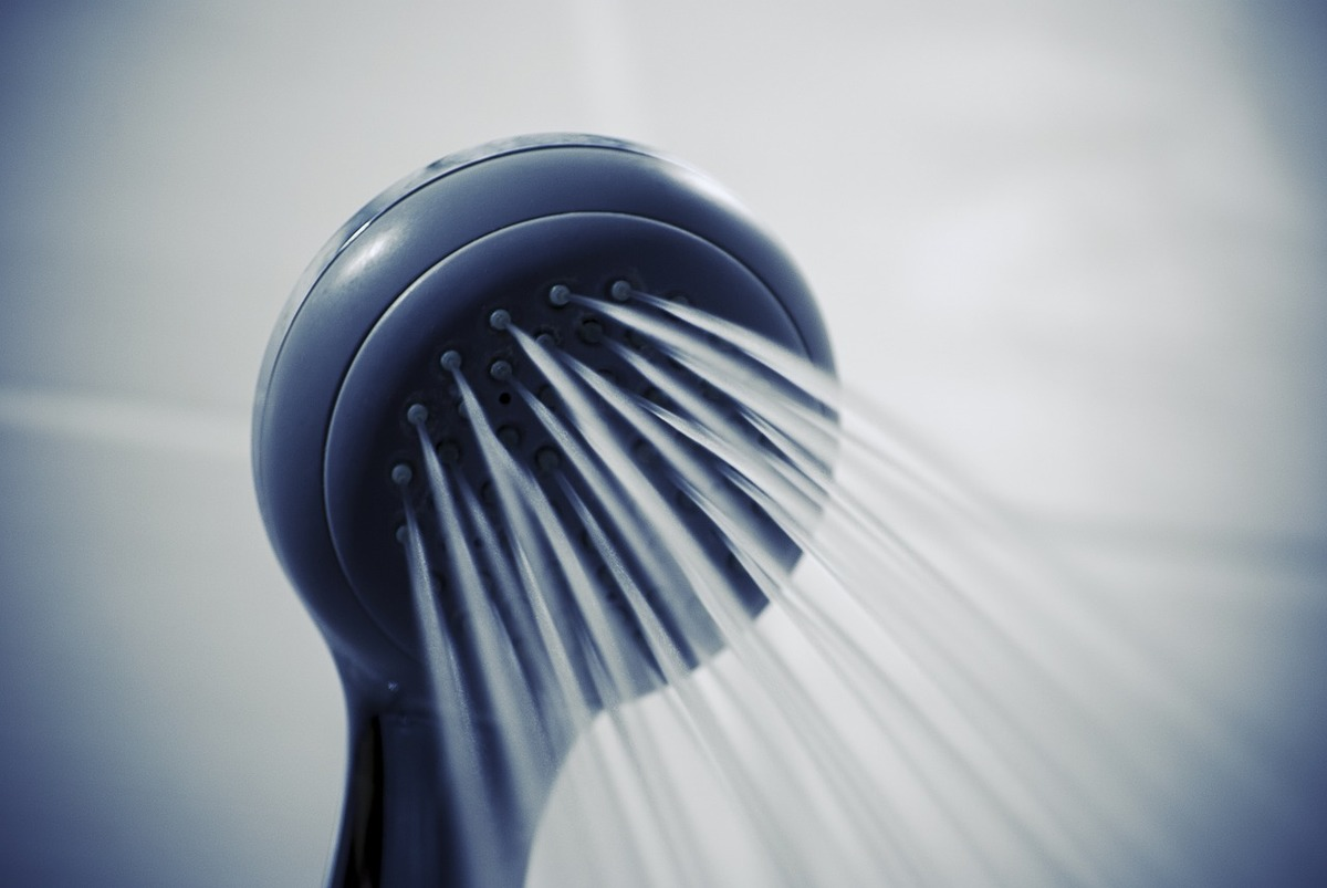Water flows out of  a shower head.