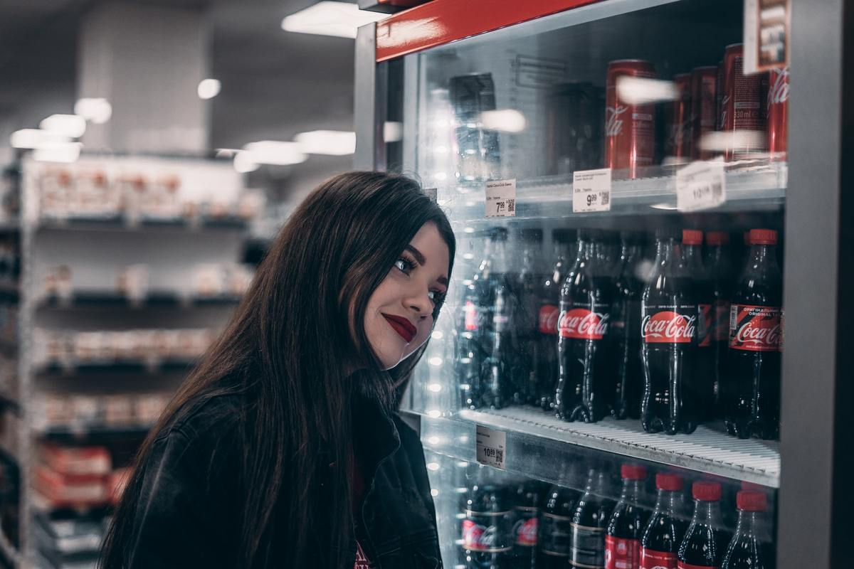 A woman browses sodas in a store.