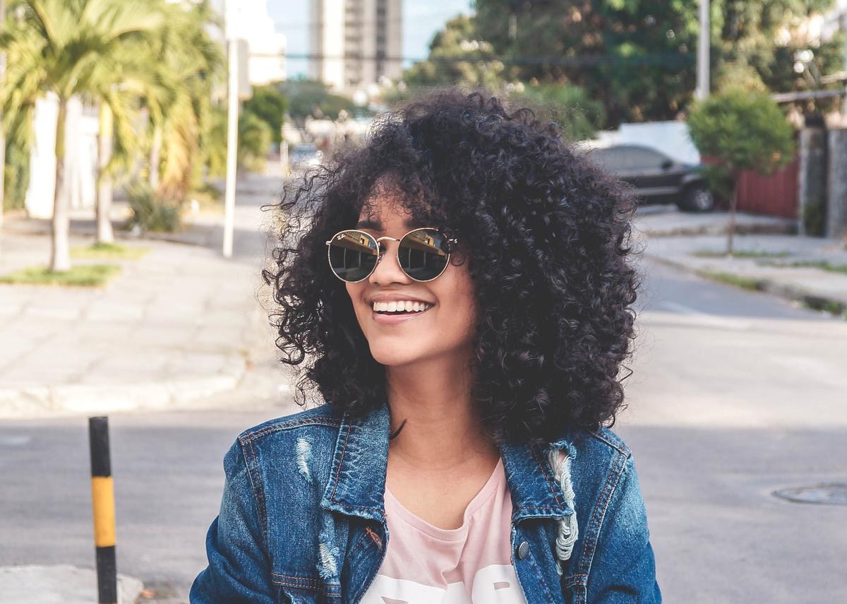 A woman wears sunglasses while walking outside.